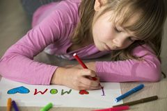 Cute child girl drawing with colorful crayons I love Mom on white paper. Art education, creativity concept.  royalty free stock photo
