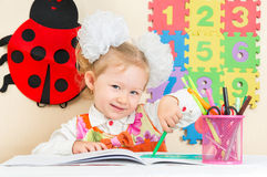 Cute child girl drawing with colorful pencils and felt-tip pen in preschool  in kindergarten. Cute child girl drawing with colorful pencils and felt-tip pen in Royalty Free Stock Photos