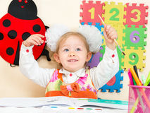 Cute child girl drawing with colorful pencils and felt-tip pen in preschool  in kindergarten Stock Image