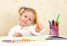 Cute child girl drawing with colorful pencils and felt-tip pen in preschool in kindergarten Royalty Free Stock Photo