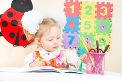 Cute child girl drawing with colorful pencils and felt-tip pen in preschool in kindergarten Royalty Free Stock Photos