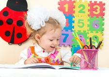 Cute child girl drawing with colorful pencils and felt-tip pen in preschool at table Stock Photos