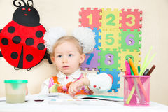 Cute child girl drawing with colorful pencils and felt-tip pen in preschool Royalty Free Stock Photo