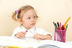 Cute child girl drawing with colorful pencils and felt-tip pen at table in kindergarten Stock Images
