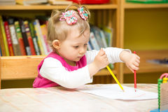 Cute child girl drawing with colorful pencils in preschool at table in kindergarten. Cute child girl drawing with colorful pencils in preschool at the table in royalty free stock images