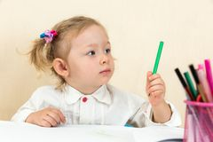 Cute child girl drawing with colorful pencils in preschool at table Royalty Free Stock Image
