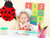 Cute child girl drawing with colorful pencils in preschool at table Stock Image