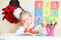 Cute child girl drawing with colorful pencils in preschool at table in kindergarten Royalty Free Stock Image