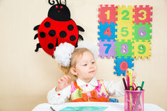 Cute child girl drawing with colorful pencils in preschool at table in kindergarten Stock Images