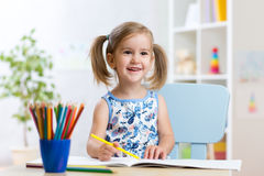 Cute child girl drawing with colourful pencils Stock Photos