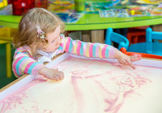 Cute child girl drawing draws developing sand in preschool at table Royalty Free Stock Photography
