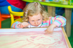Cute child girl drawing draws developing sand in preschool at table in kindergarten Stock Photos