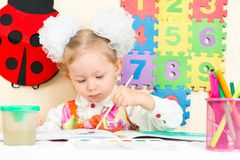 Cute child girl drawing in preschool at table in kindergarten Royalty Free Stock Image