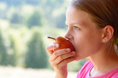 Cute child girl eating pear Stock Photography