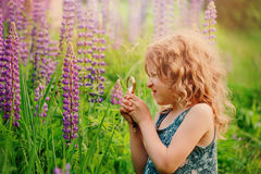 Cute child girl exploring nature with loupe on summer field Stock Photos