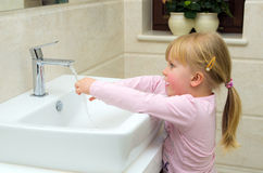 Child washing hands. A cute child (girl of four years old) washing her hands in bathroom Stock Photo