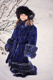 Cute child girl in fur coat in winter forest Royalty Free Stock Photo