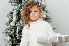 Cute child girl with gift near Christmas tree Stock Photos