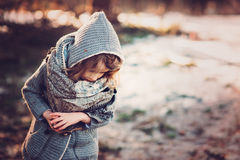 Cute child girl in grey knitted coat plays on the walk in winter forest Stock Photos