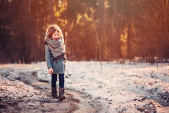Cute child girl in grey knitted coat plays on the walk in winter forest Royalty Free Stock Images