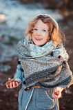 Cute child girl in grey knitted coat plays on the walk in winter forest Stock Photography