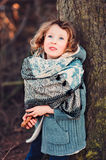 Cute child girl in grey knitted coat plays on the walk in winter forest Royalty Free Stock Photos