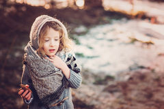 Cute child girl in grey knitted coat plays on the walk in winter forest Royalty Free Stock Photo