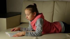 Cute child girl in grey pink sweatshirt lies on couch in room and reads book stock video footage