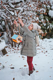 Cute child girl hangs bird feeder in winter snowy garden Royalty Free Stock Image