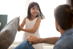 Cute child girl having funny pillow fight with dad. Cute little child girl laughing holding cushion having funny pillow fight with dad, happy joyful kid daughter royalty free stock photos