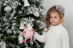Cute child girl hold sheep toy on Christmas tree Stock Photos