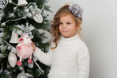 Cute child girl holds sheep toy on Christmas tree. Cute child girl with sheep toy on Christmas tree Stock Photography