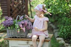 Cute child girl making lilac wreath in spring blooming garden Royalty Free Stock Photos