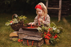 Cute child girl making rowan beads in autumn garden Royalty Free Stock Photos