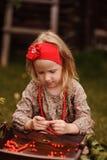 Cute child girl making rowan berry beads in autumn garden Stock Images