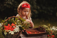 Cute child girl making rowan berry beads in autumn garden Royalty Free Stock Photo