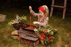 Cute child girl making rowan berry beads in autumn garden Stock Images