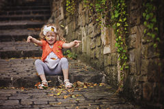 Cute child girl in orange cardigan throwing leaves while sitting on stone road Stock Image