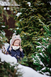 Cute child girl in owl knitted hat on the walk in winter snowy garden Stock Photos