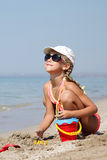 Cute child girl playing on beach. Sitting on the sand in a bathing suit raised her head up Royalty Free Stock Images