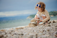 Cute child girl playing and building rock tower on summer beach Royalty Free Stock Photo