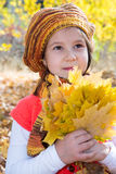 Cute child girl playing with fallen leaves in autumn Royalty Free Stock Photos