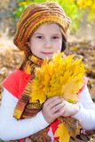 Cute child girl playing with fallen leaves Stock Photography