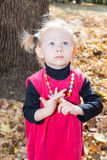 Cute child girl playing with fallen leaves in  park Royalty Free Stock Image