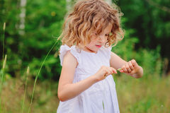Cute child girl playing with grass on the walk in summer forest Royalty Free Stock Image