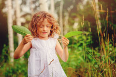 Cute child girl playing with green leaves in summer forest Stock Photography