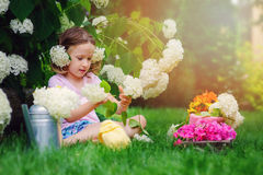 Cute child girl playing and making flower bouquet in summer garden Royalty Free Stock Photo