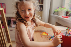 Cute child girl playing with mosaic at home in her room Stock Image