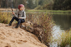 Cute child girl playing on the river side. Cute child girl in knitted hat and sweater playing with stick on the river side Stock Photo