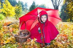 Cute child girl playing with umbrella in leaves in autumn Stock Photography